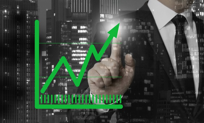 Man in suit pointing at screen showing upward green arrow on chart