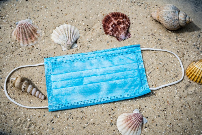 A light blue surgical mask lying on a sandy beach surrounded by seashells