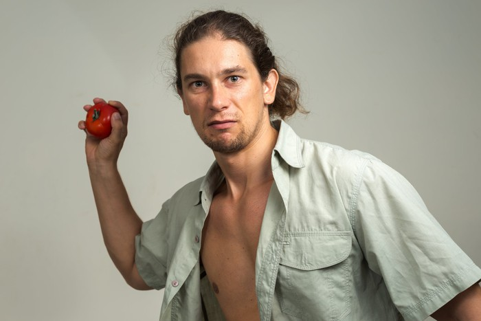 A man cocks his arm to throw a tomato.