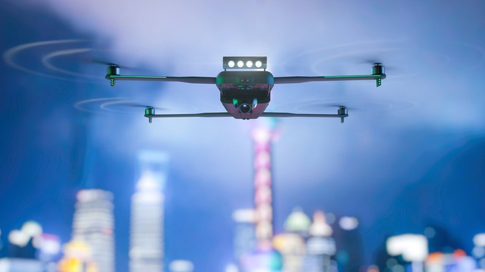 A drone in flight, with a city in the background.