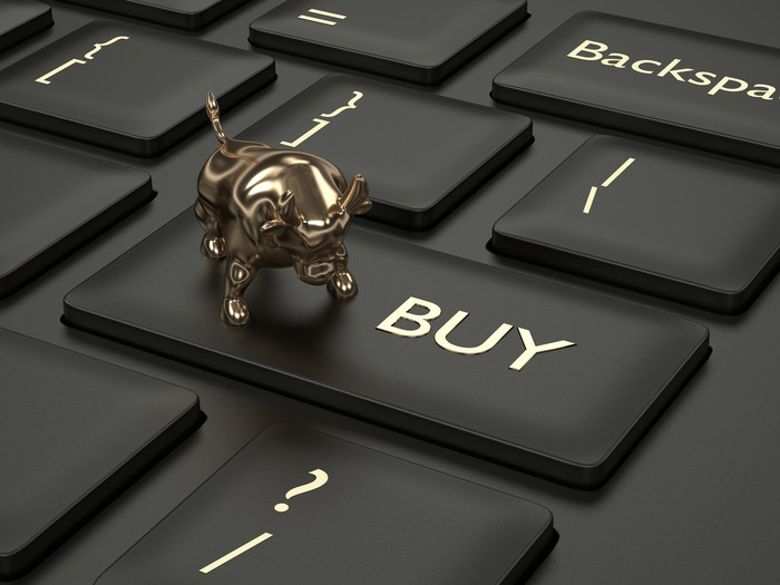 A miniature bull is on top of a keyboard button labeled buy.