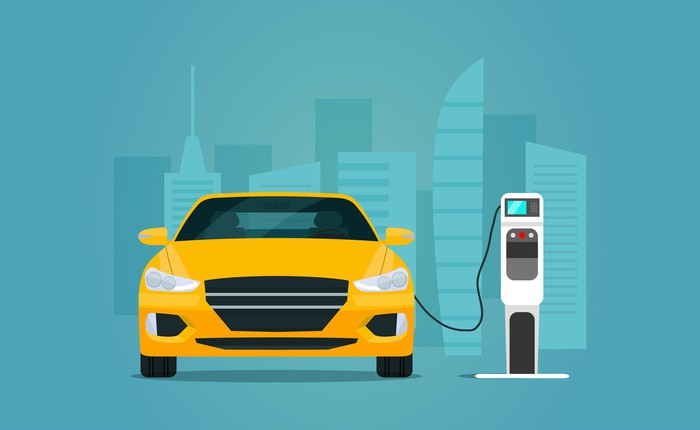 Cartoon of a yellow car plugged into an electric charging station.