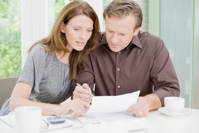 Couple reviewing finances and retirement plan together at home.