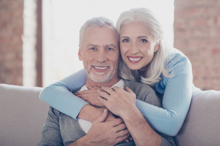 Older woman wrapping arms around older man seated on couch
