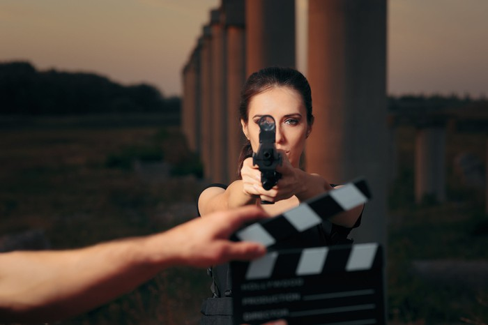 A generic superhero film actress pointing a gun at the camera, a hand holding a clapperboard in the foreground, and pillars in the background.