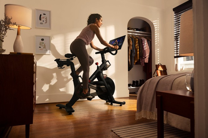 A woman rides her Peloton bike in her bedroom near a bed and a dresser