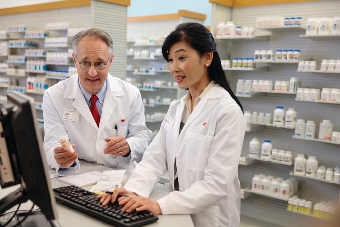 Two CVS pharmacists collaborating while using a computer.
