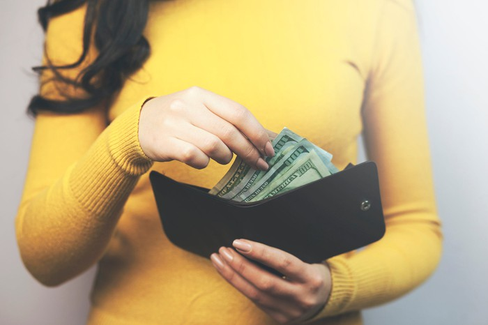 A woman reaches into her wallet filled with $100 bills.