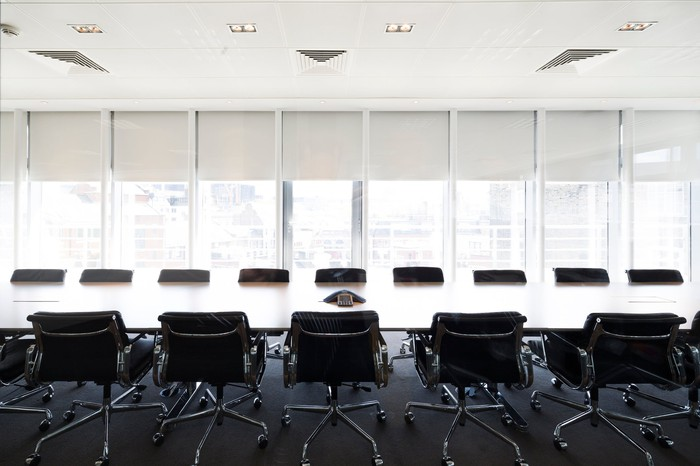 An ultramodern corporate boardroom with rows of chairs flanking a long polished tabletop.