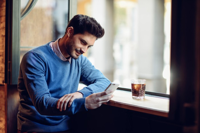 A man uses his phone while drinking a cola.