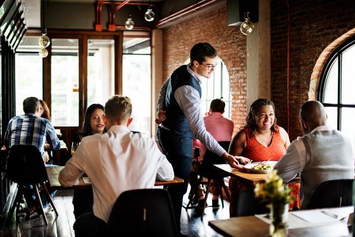 A waiter serves a table.