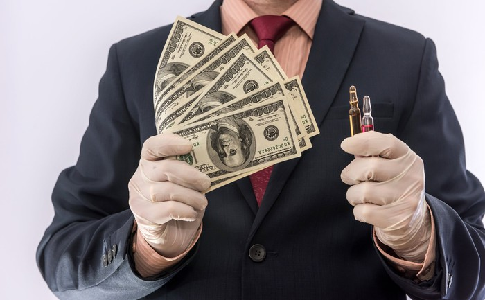 Man in suit wearing gloves holding cash and vials