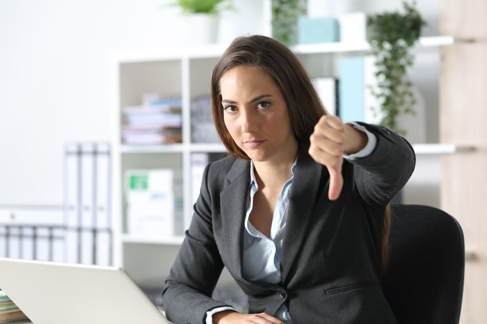 Woman in business suit at laptop giving thumbs down sign
