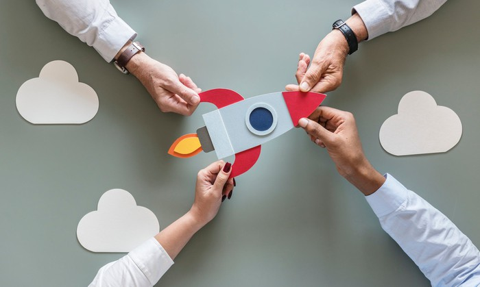 Teamwork concept: Four hands are pictured holding a cardboard cutout of a rocket ship.
