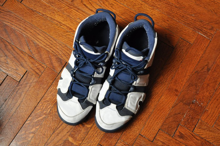 A pair of blue and white basketball shoes on a herringbone wood floor.
