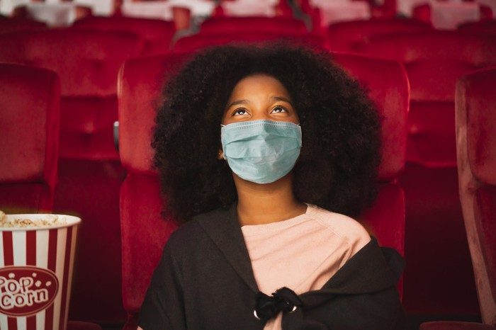 Young girl wearing face mask sitting in a movie theater with a popcorn bucket beside her