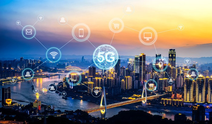 A city skyline. A bubble with 5G is illustrated along with other bubbles containing electronic devices.