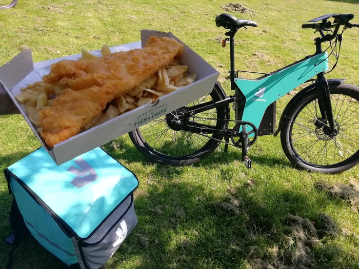 A Deliveroo marked bicycle and delivery pouch resting on grass, with a hand holding a box of fish and chips in the foreground.