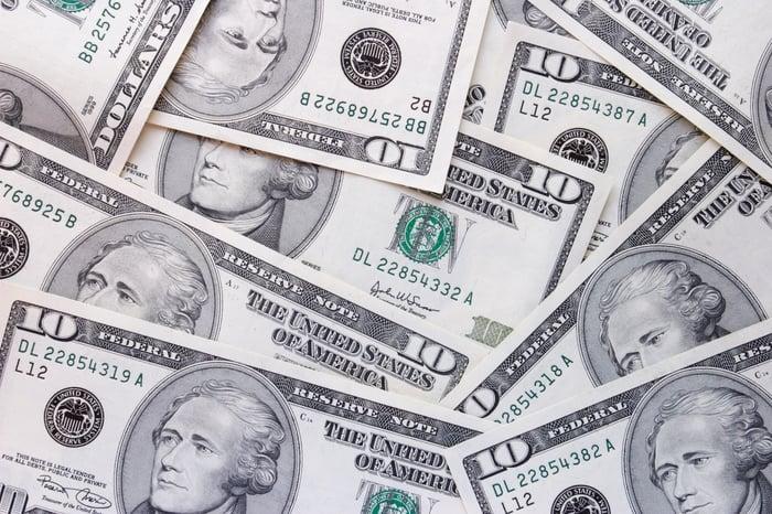 U.S. ten dollar bills scattered.
