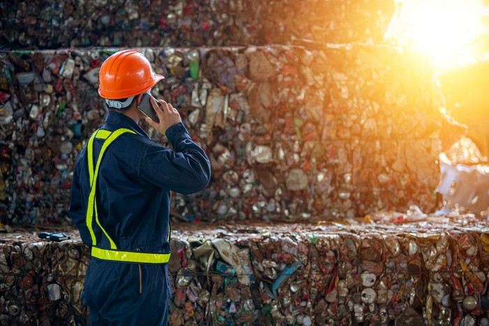 A worker manages the process of packing waste for recycling.