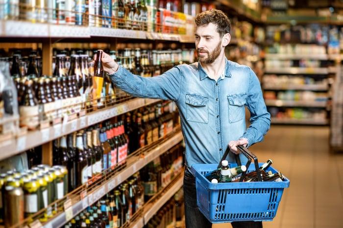 A man shops for beer at a supermarket.