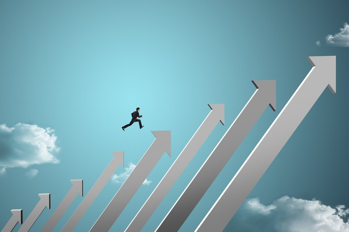 A series of up arrows against a blue sky, with a businessman running up them.