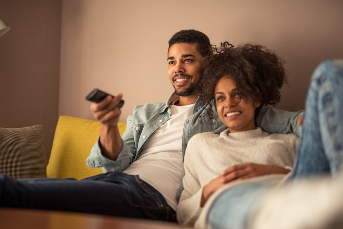 Man on couch holding TV remote while woman leans on him