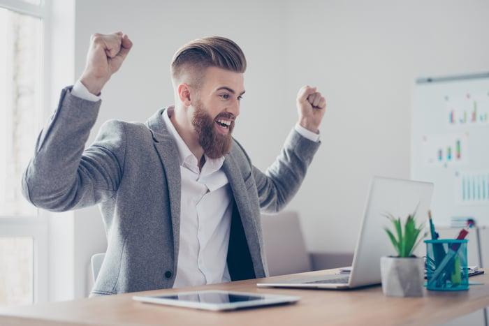 Man at laptop raising his arms and smiling