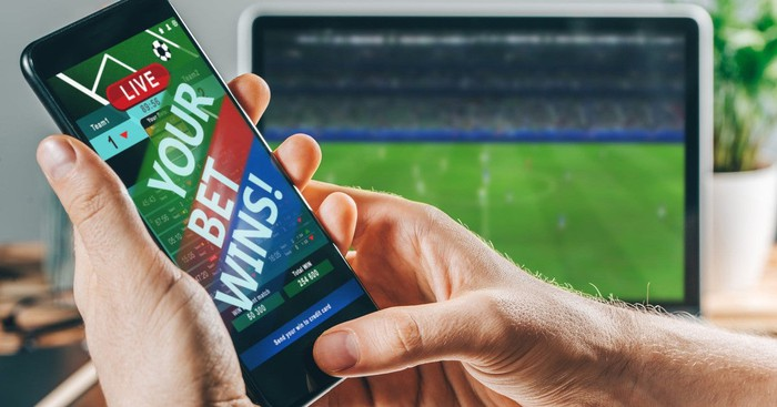 Smartphone with screen saying Your Bet Wins next to computer showing soccer game.