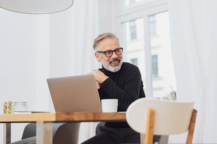 Smiling older man sitting at laptop