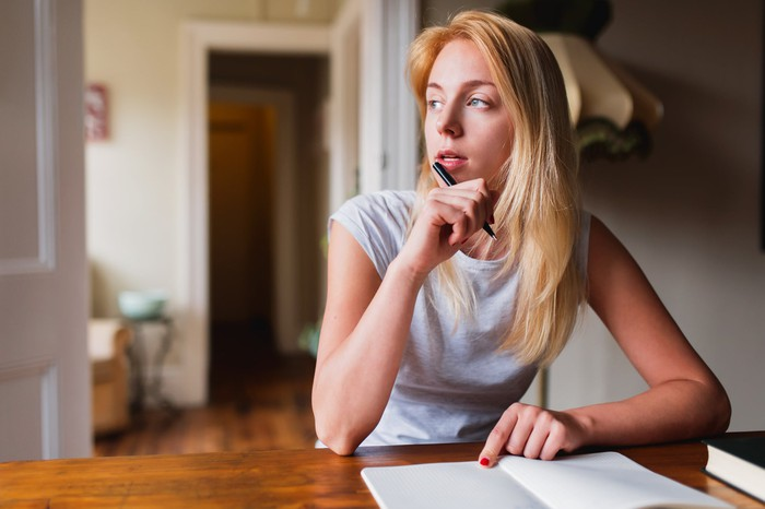 Woman with pen and notebook looking off into the distance thinking