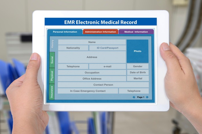 an electronic medical record on a tablet held by two hands
