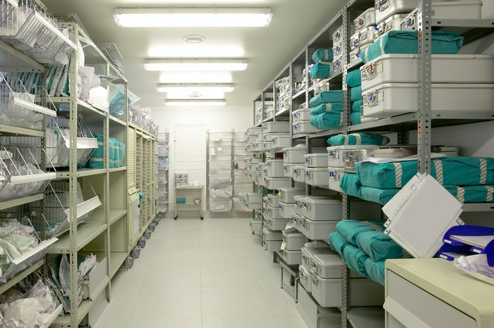 A storeroom of medical supplies in bins stacked floor to ceiling.