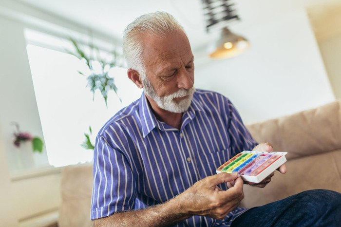 Older person holding a pill case.