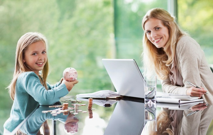 Adult sitting at a table with an open laptop opposite a child with coins on the table and a piggy bank in her hand.