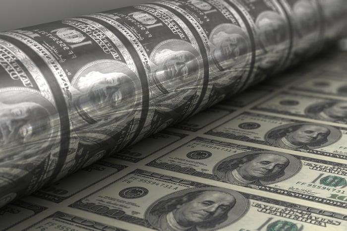 A printing press churning out crisp one hundred dollar bills.
