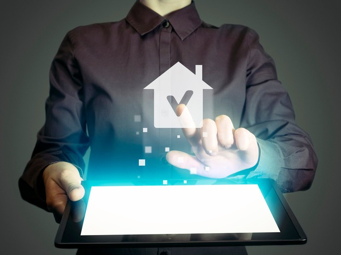 Person holding tablet with house graphic hovering above