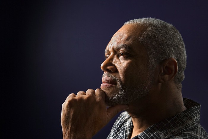 A senior man thinks as he rests his chin on his hand.