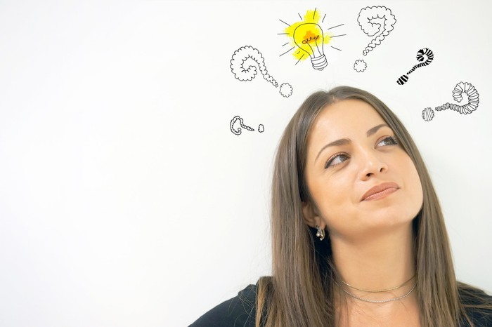 A woman looks up at illustrations of question marks and a light bulb over her head