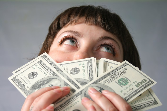 Woman holding lots of $100 bills in front of her face