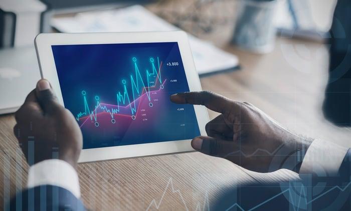 Man holding a tablet displaying rising charts.