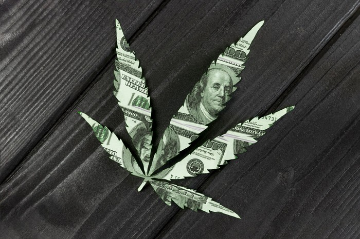 Cannabis leaf made from $100 bill on a wooden surface.