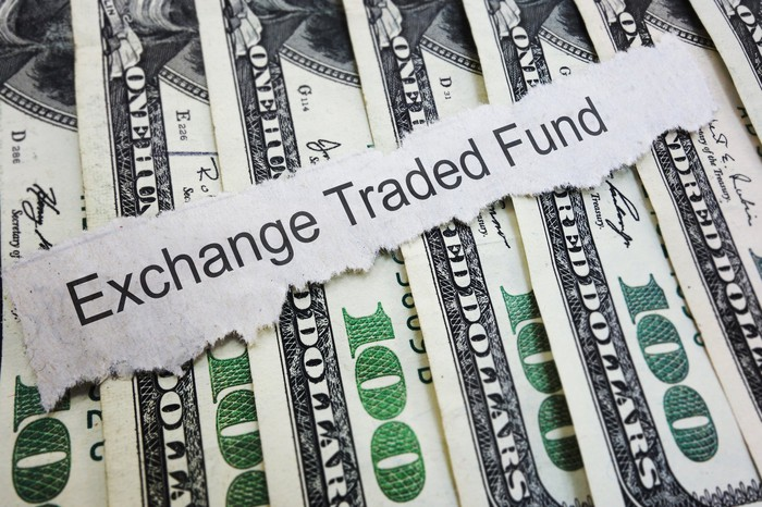 """""""Exchange Traded Fund"""" printed on a slip of paper laid atop a stack of $100 bills."""