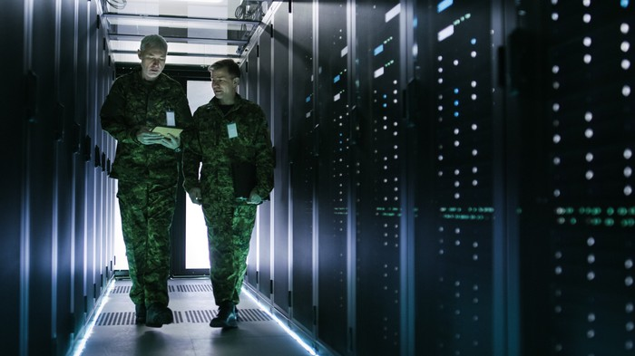 Two military personnel in fatigues walk among a row of servers.