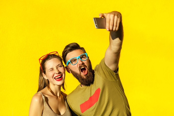 Couple mugging in front of a smartphone