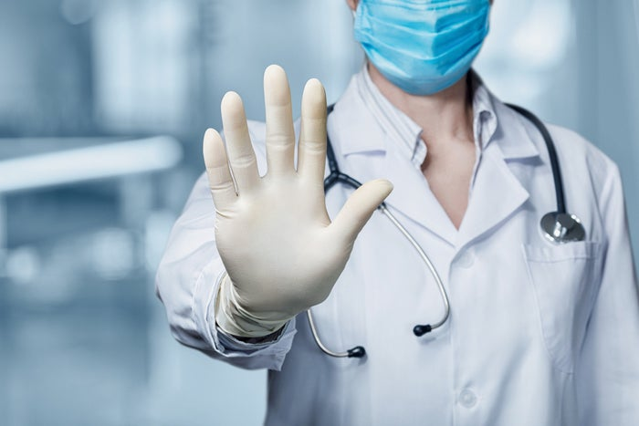 Doctor wearing a mask holding hand up with palm forward