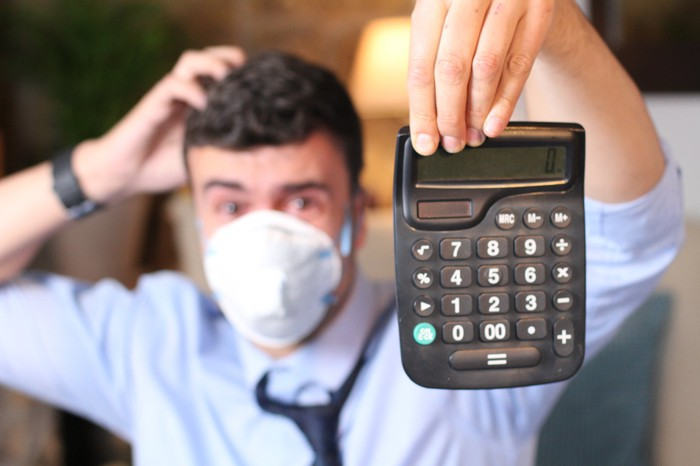 A man wearing a mask and holding a calculator.