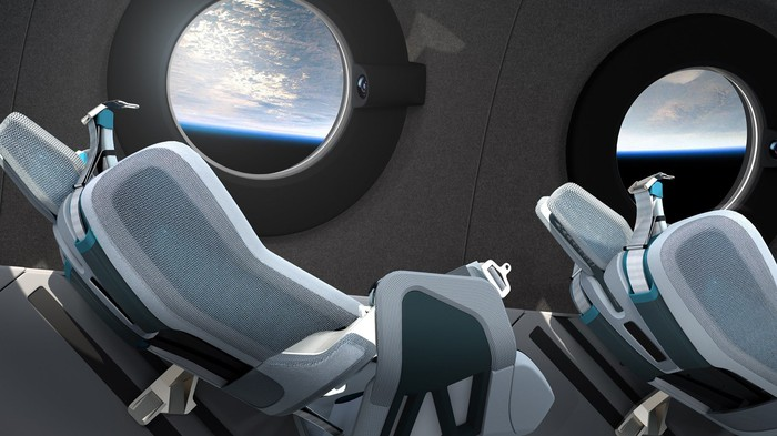 Reclining seats with portholes showing Earth from orbit.