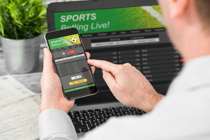 Sports betting online with smartphone and laptop.