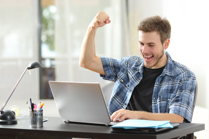 Man looking at laptop with hand raised triumphantly.